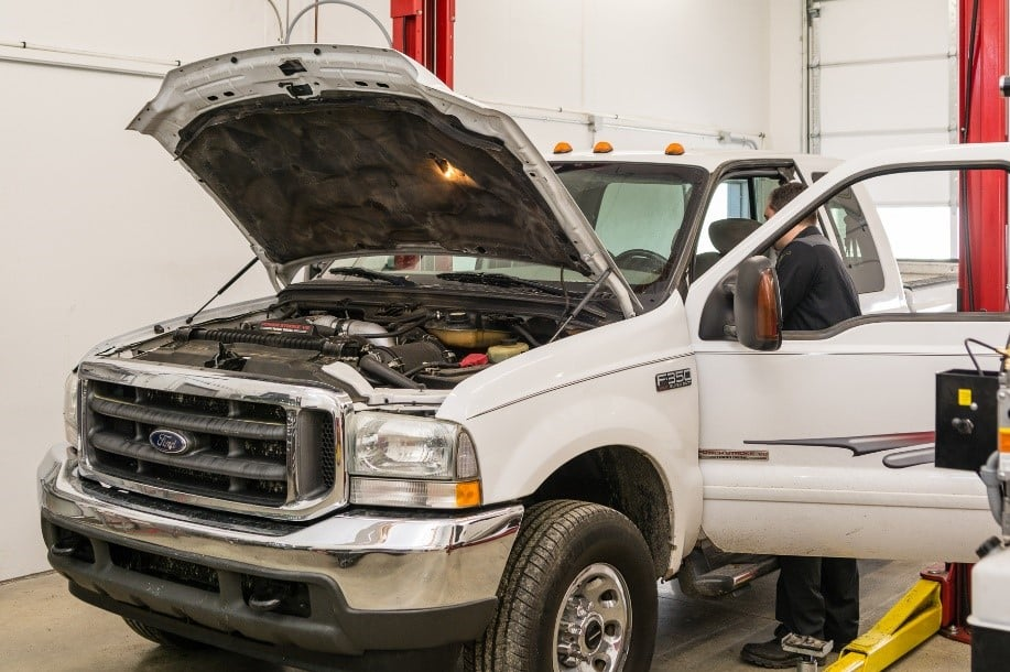 A white Ford F-350 with an open hood and under inspection in an auto repair garage