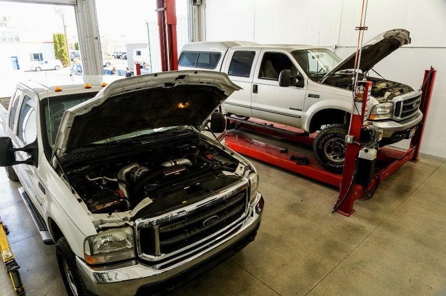 Two white Ford F-series pickup trucks with open hoods under repair in an automotive shop